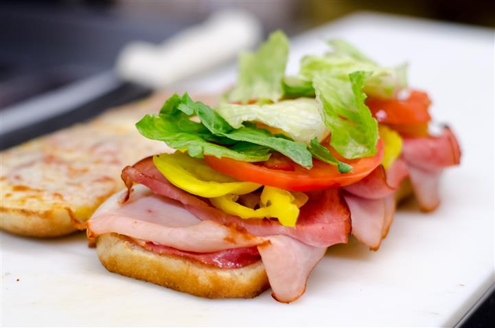 Sandwich consisting of ham tomatoes and lettuce
