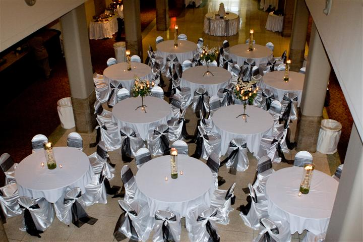 multiple tables decorated with white cloth and center pieces