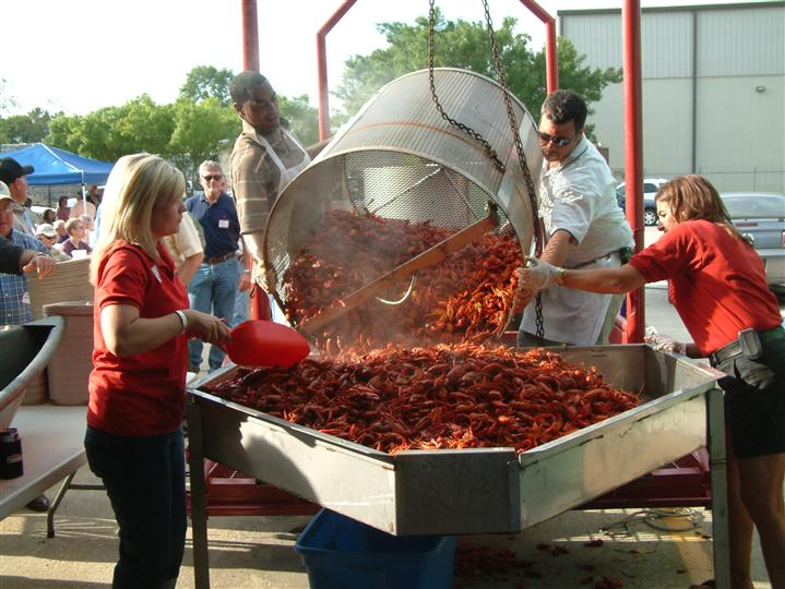 employees emptying out a crate of crawfish onto a table