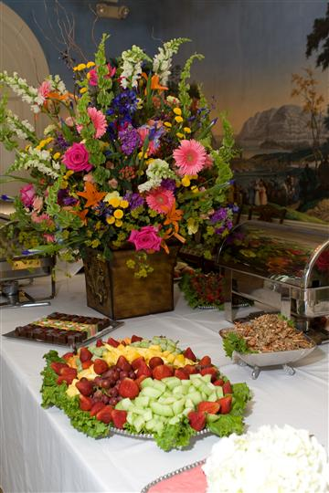 catering table serving a fresh assortment of fruit decorated with a pot of flowers