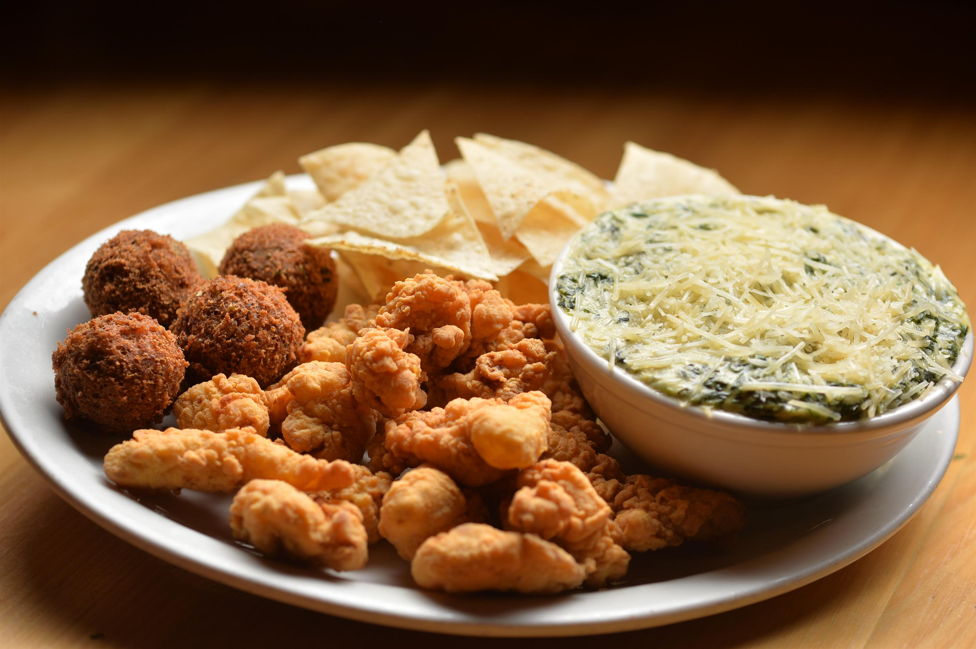 spinach dip and chips with popcorn chicken and hush puppies