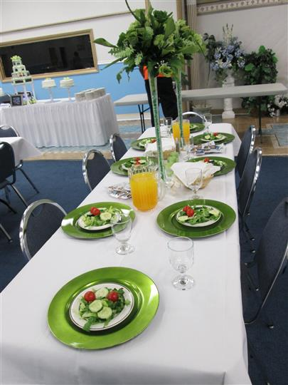 A rectangular 8-seat table having 2 jugs of orange juice and 8 fresh salad dishes in green colour on it