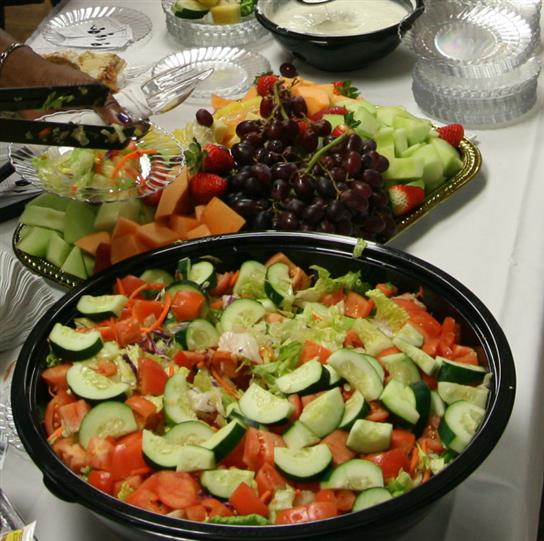 A Greek salad tray and a fresh fruit tray