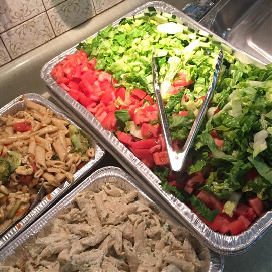 a fresh salad tray and two pasta salad trays