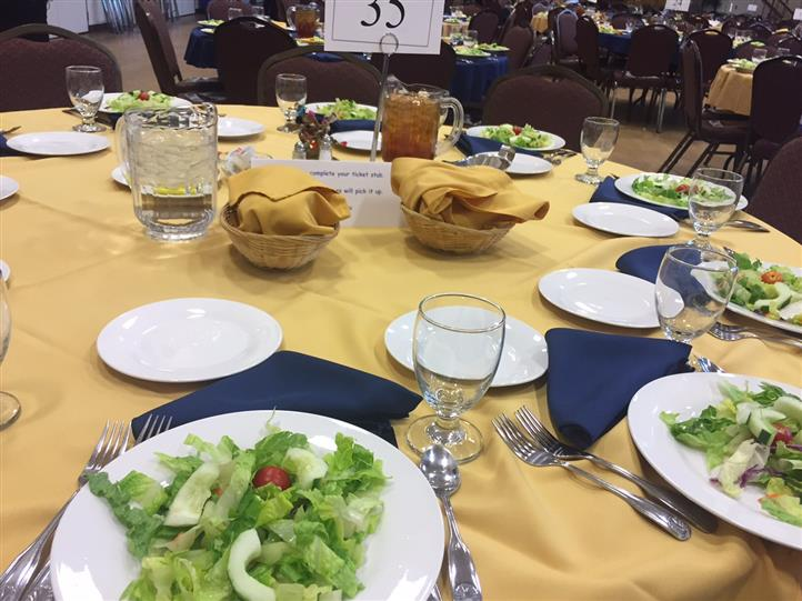 10- seat round tables with yellow tablecloth and blue napkins