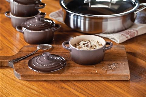 Assorted cookware on table with food in bowl on cutting board.