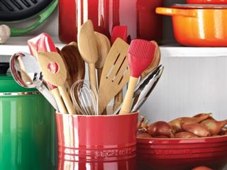 Le Creuset Utensil Crock holding wooden spoons, whisk, spatulas