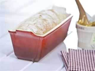 Le creuset loaf pan with loaf of bread on table