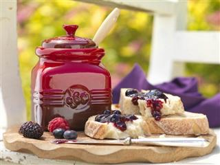 Le Creuset berry jam spread on bread on carving board