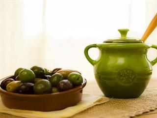 Le creuset olive jar next to dish of olives