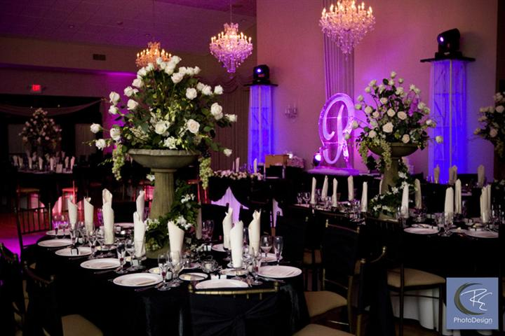 Interior shot of a decorated reception hall with white flowers and violet lights