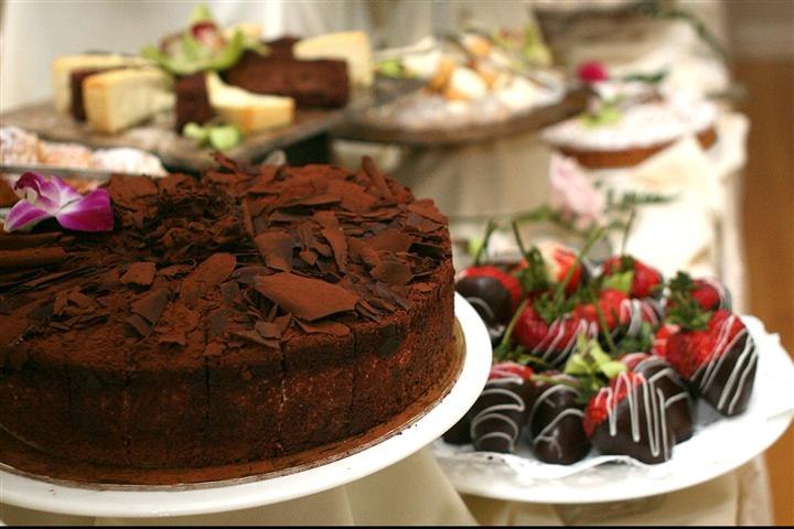 A chocolate cake, and strawberries covered with chocolate