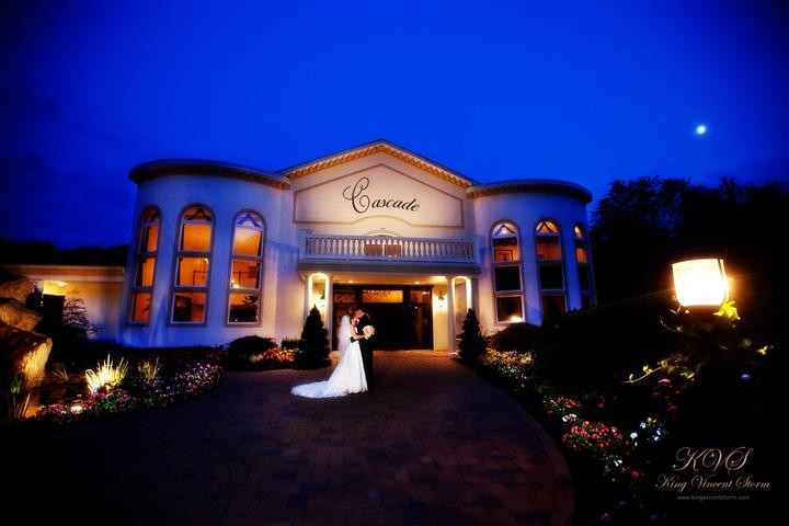 Night photo of a bride and a groom outside the Cascade Fine Catering building