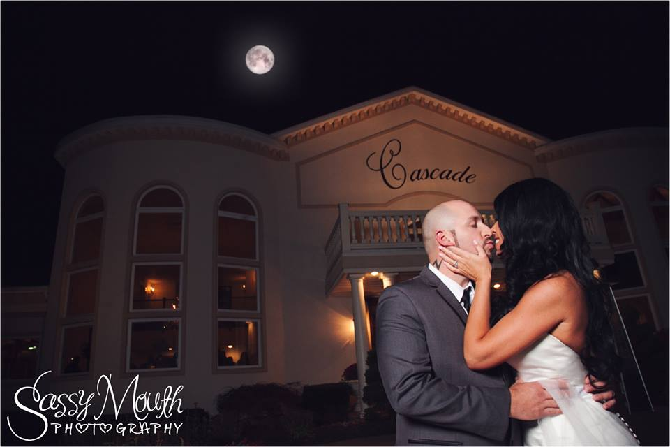Outdoor night shot of a kissing couple outside the Cascade Fine Catering building