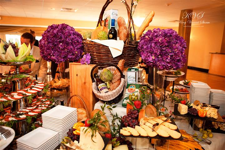A decorated buffet with breads, flowers and several food trays
