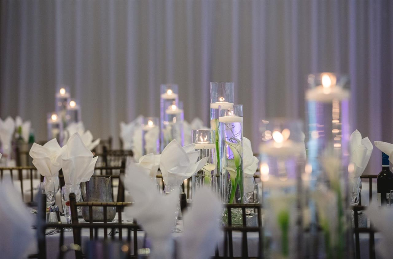 Candles and flowers of a white and transparent decoration of the reception tables