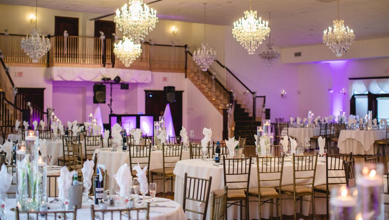 An interior shot of reception hall with white decoration and violet lights