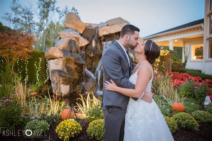 A bride and a groom kissing in the garden