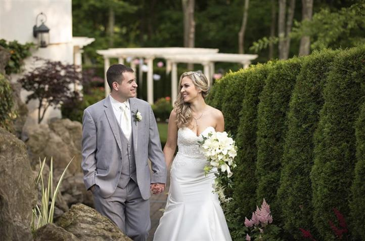 A bride and a groom while walking in a garden