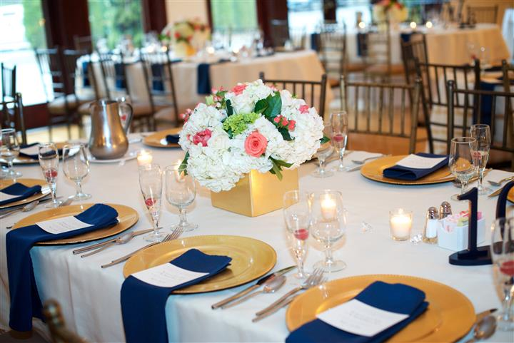 Interior shot of a reception hall with yellow dishes and dark blue napkins
