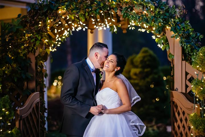A bride and a groom kissing in the garden at night