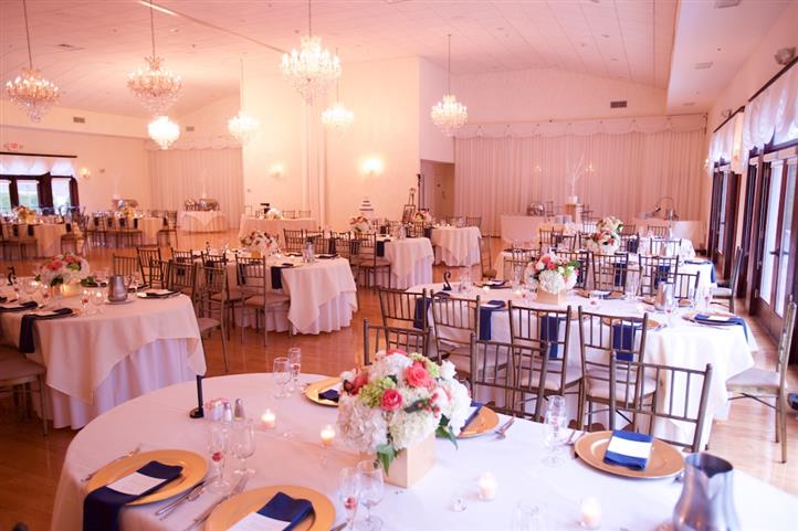 Interior shot of a reception hall with white table cloths and dark blue napkins
