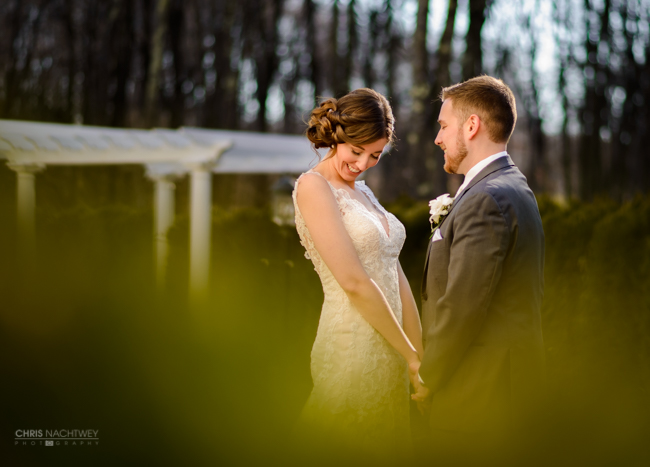 An outdoor photo of a bride and a groom holding hands