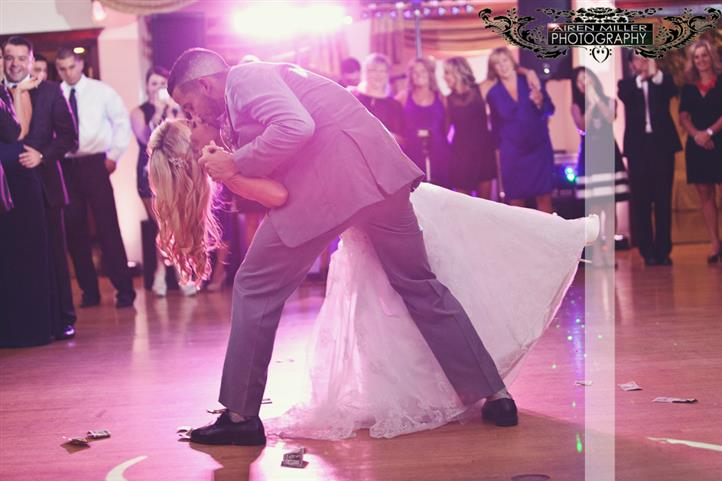 A kissing couple while dancing at their wedding