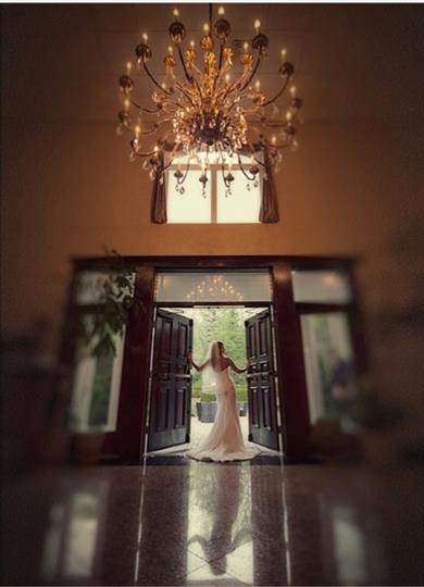 Interior shot of a bride standing at the entrance of a building