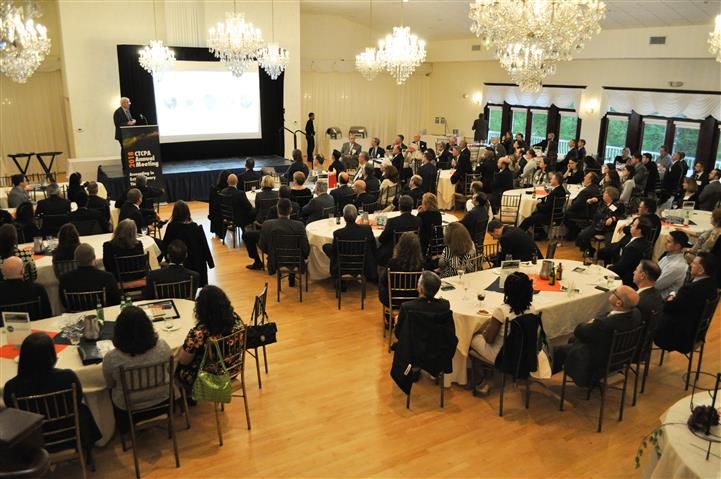 A reception hall with people sitting at the dining tables watching a presentation