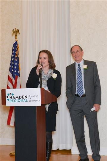 A photo of a woman giving a speech at a chamber of commerce reception