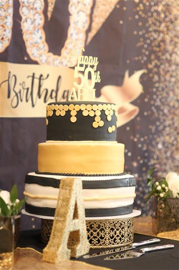 Three level birthday cake with black, yellow and white decoration