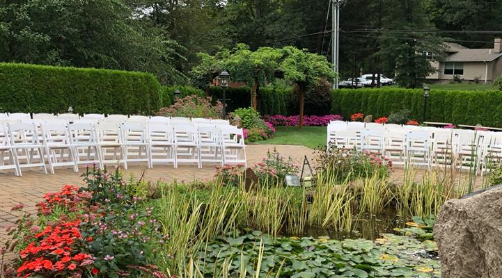 Outdoor shot of white chairs by a lake at the garden