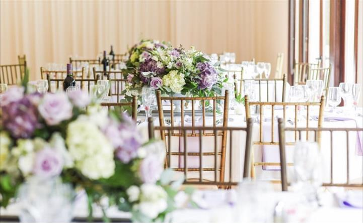 White and violet bouquets and decoration of tables in a reception hall