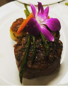 Grilled steak decorated with asparagus, and an orchid