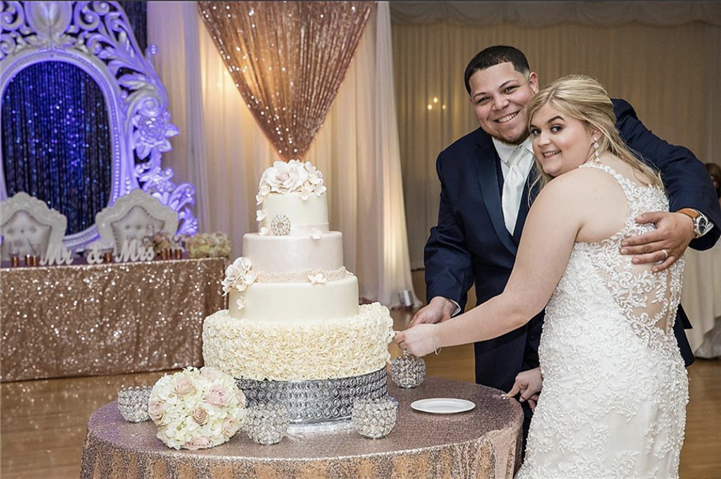 A bride and a groom while cutting their four level wedding cake