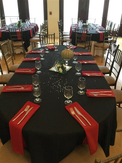 Interior shot of the tables with black table cloths and red napkins in a reception hall