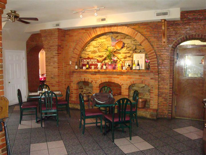 interior dining area with tables and chairs with a brick wall covered with decorations