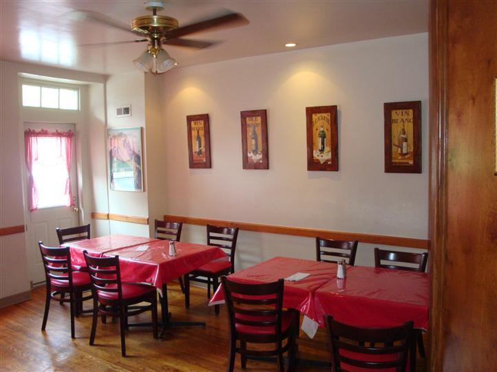 interior dining area with tables and chairs with paintings on the wall