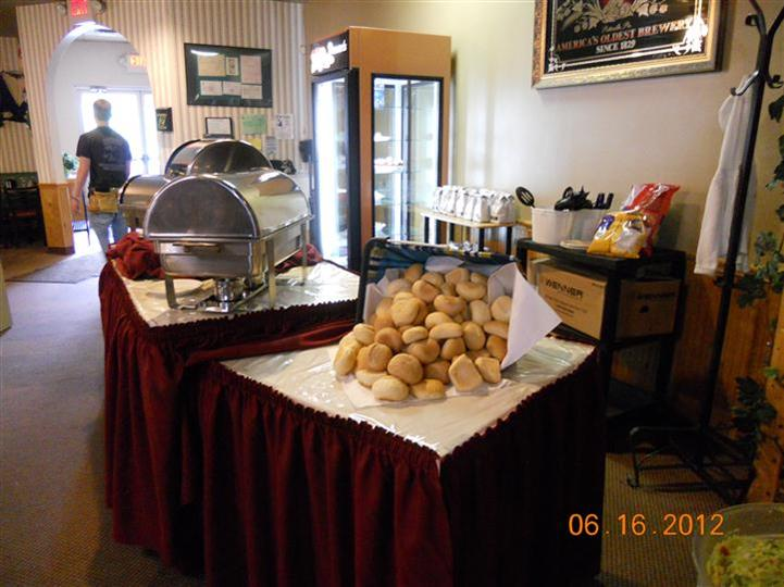 a buffet table with a basket of rolls