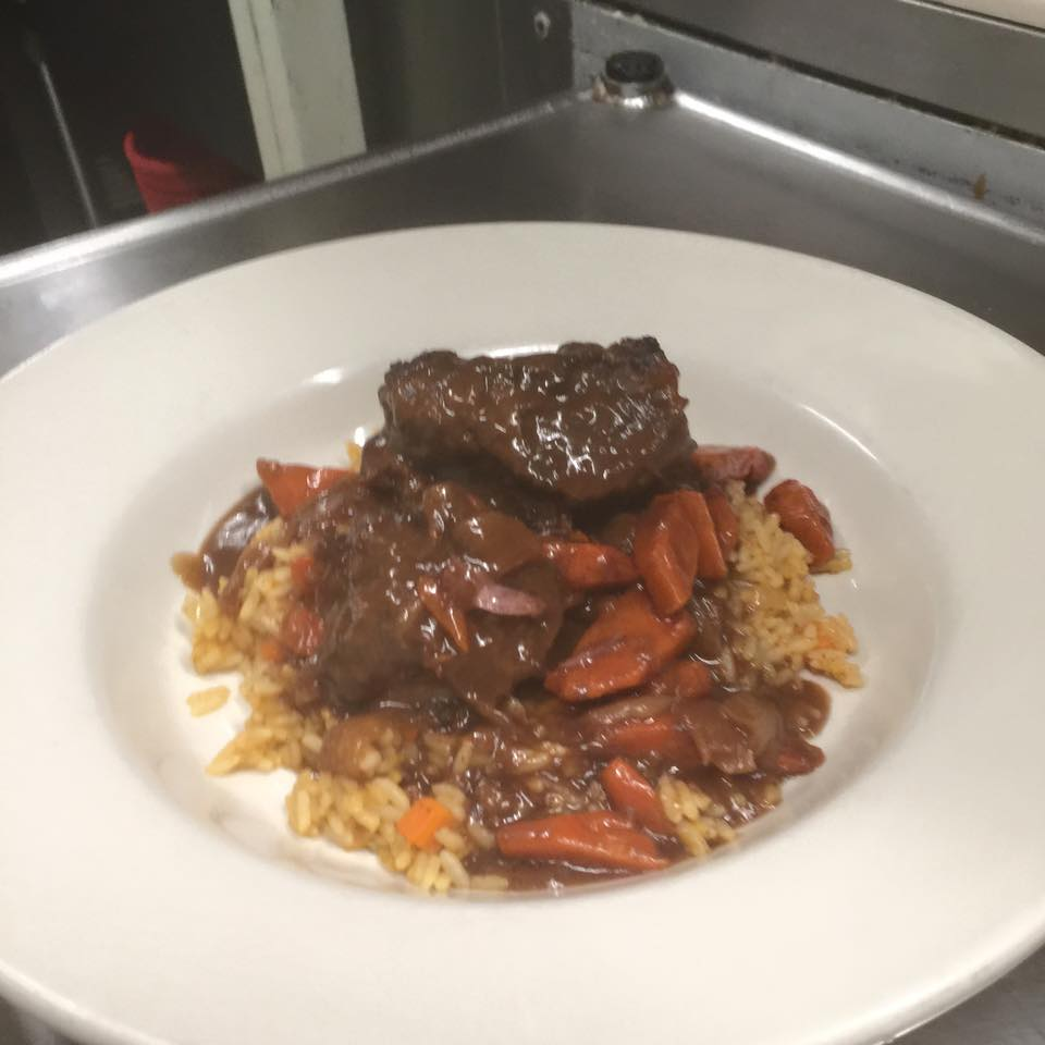a plate of beef and carrots covered in gravy over rice