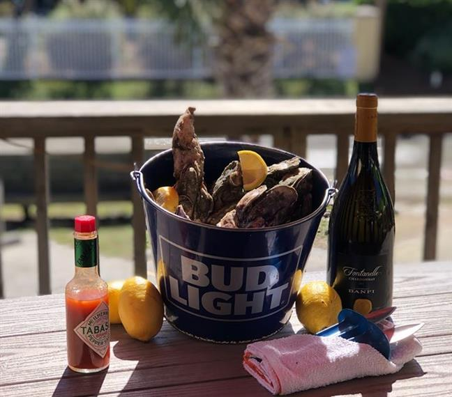 oysters in a bucket with lemons, hot sauce and a bottle of wine.