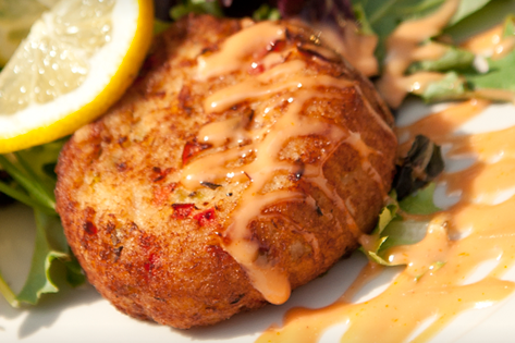 crabcake with sauce and lemon slice