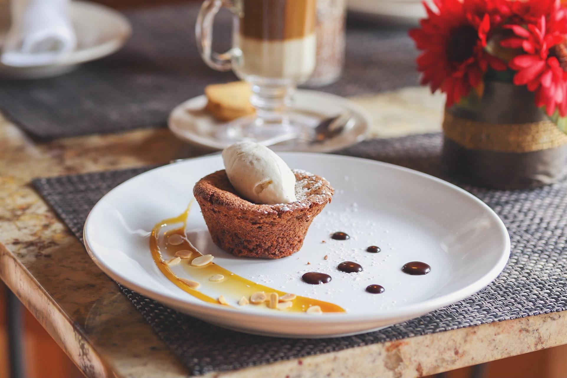 warm flourless chocolate cake served with chopped roasted almonds and topped with vanilla ice cream