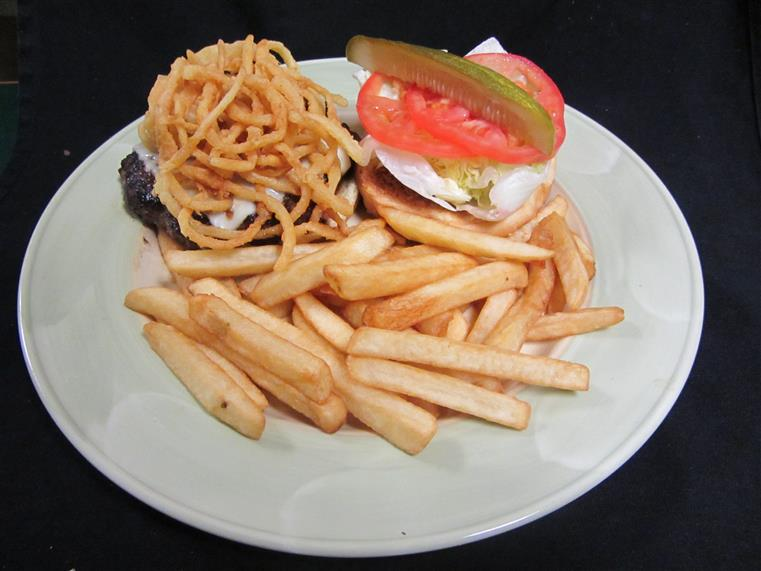 Open faced burger covered with cheese, onion straws next to bun with lettuce, pickle, tomatoes, side of thick fries on a dish.