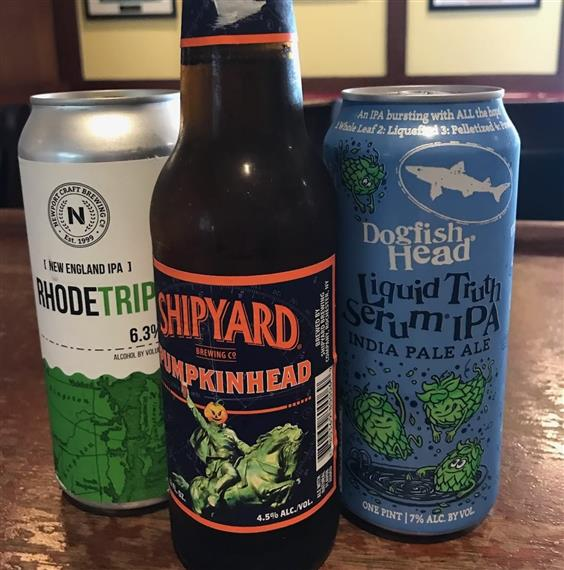 Closeup of two beer cans and beer bottle on table. Rhode trip, shipyard pumpkin head, dogfish head