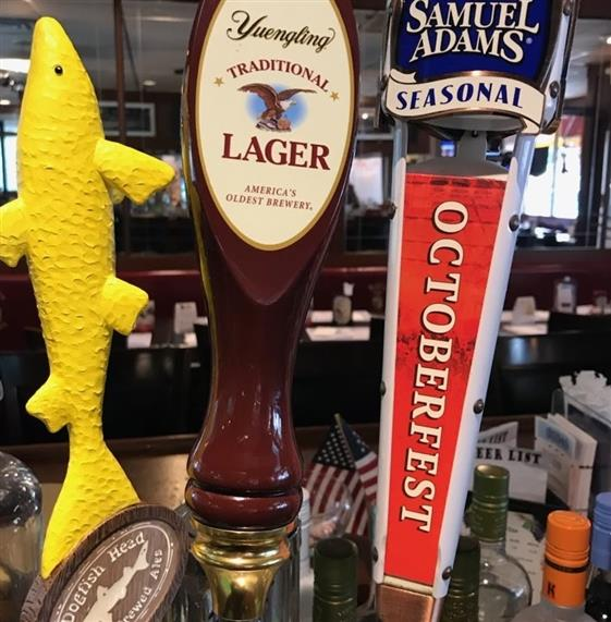 Closeup of beer taps - dogfish head, yuengling traditional lager, samuel adams seasonal octoberfest