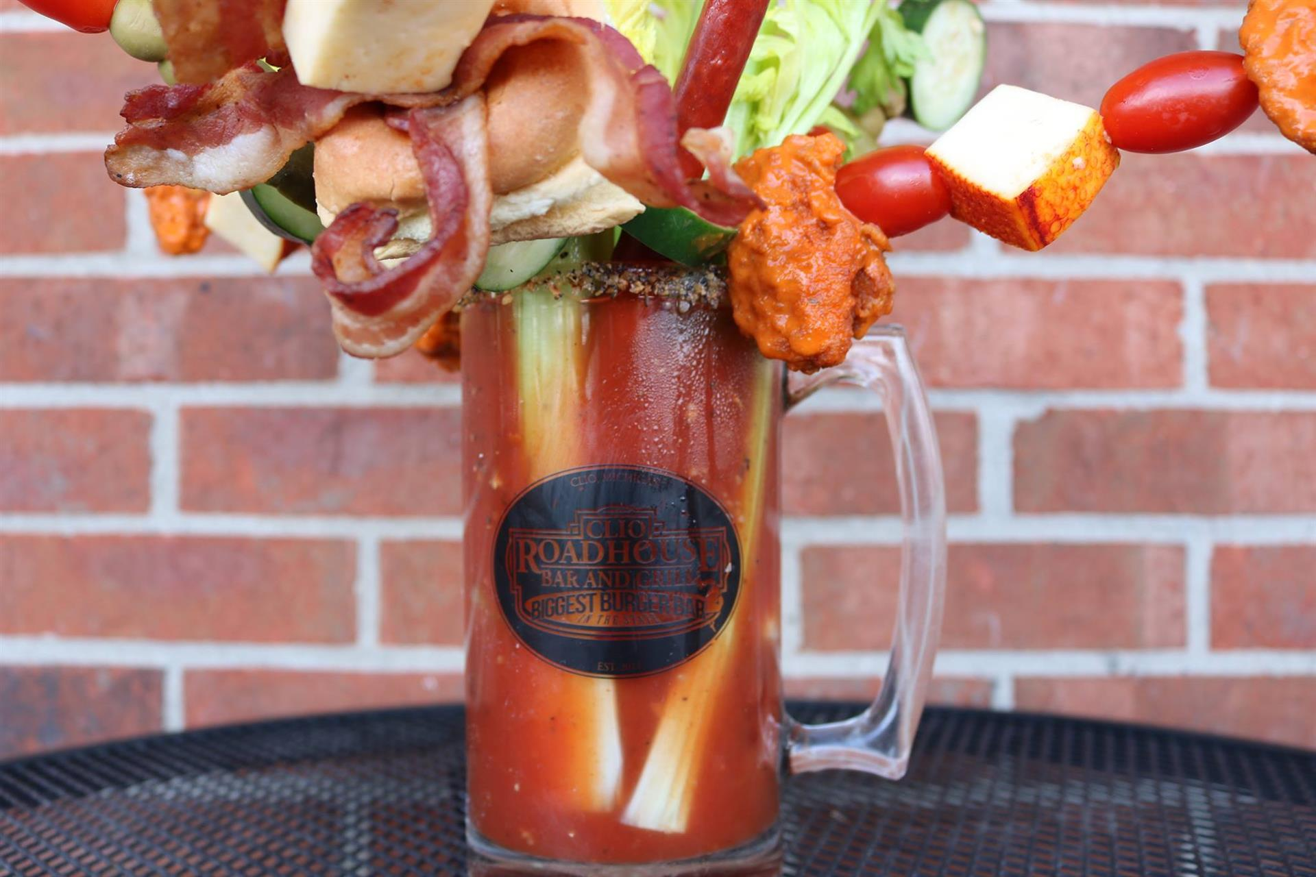 bloody mary with celery, bacon, tomatoes, bonesless chicken bites, and a burger