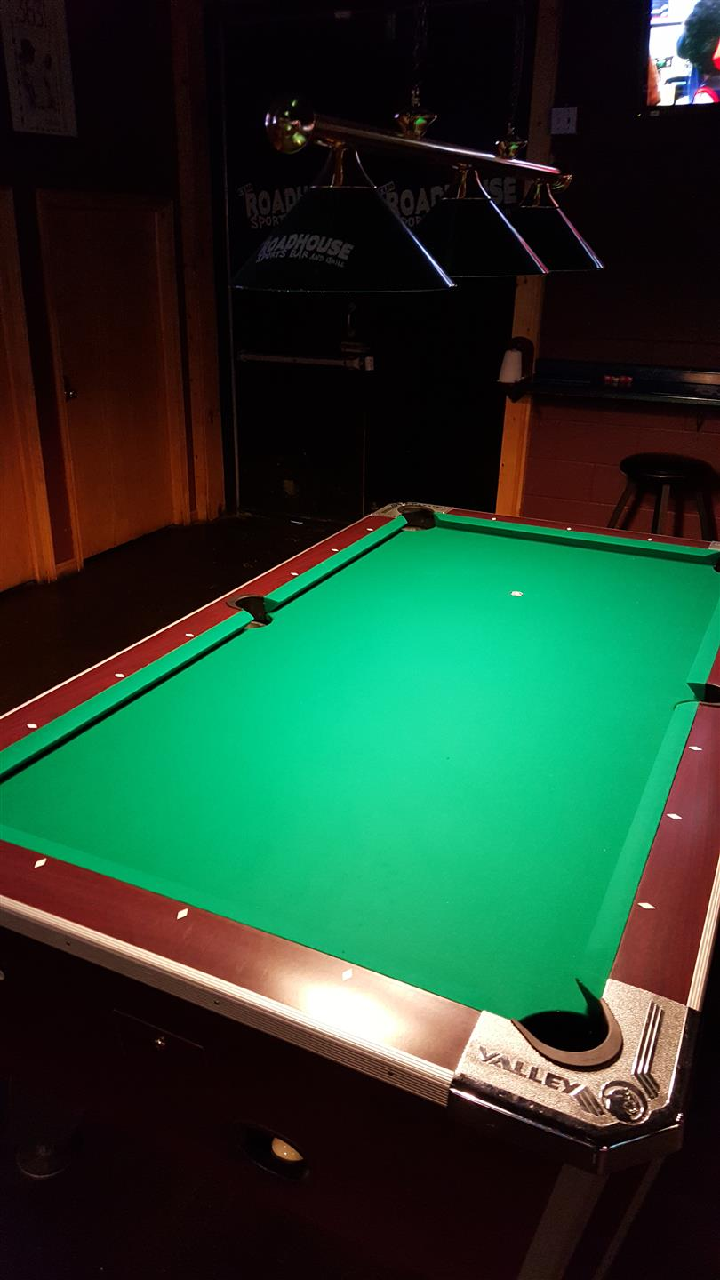 pool table in a room with benches