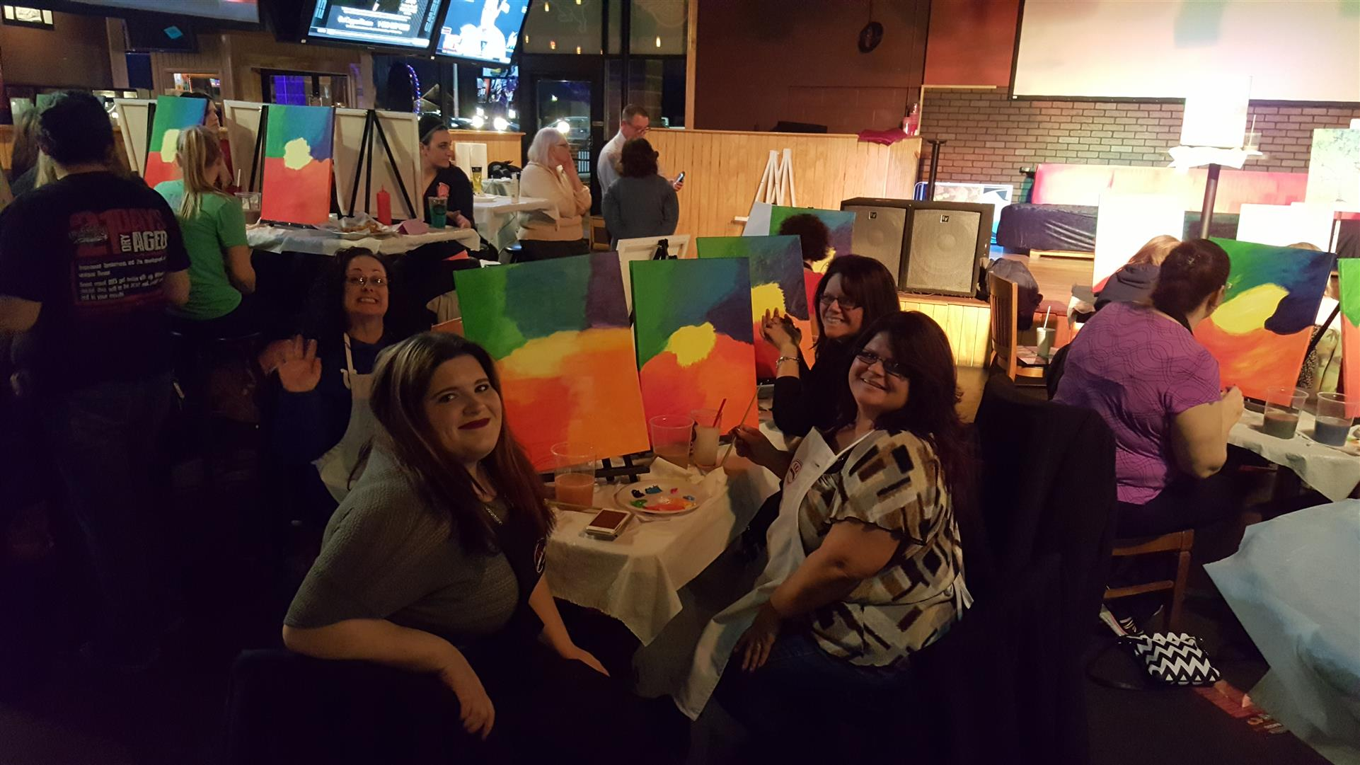 group of people sitting at a table for paint night with painted canvas's